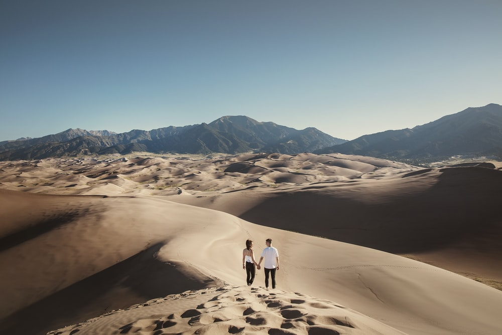2 person walking on sand during daytime