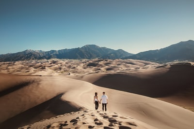 A couple holding hands on top of High Dune in Great Sand Dunes National Park, Colorado.  Explore more at explorehuper.com