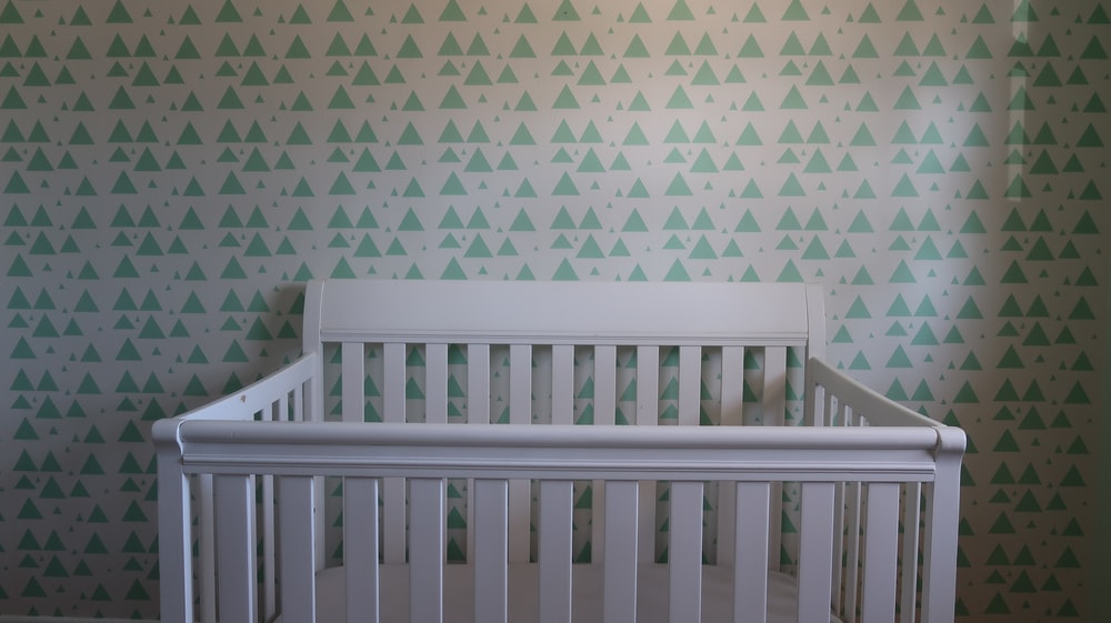 white wooden crib with white and blue polka dot wall