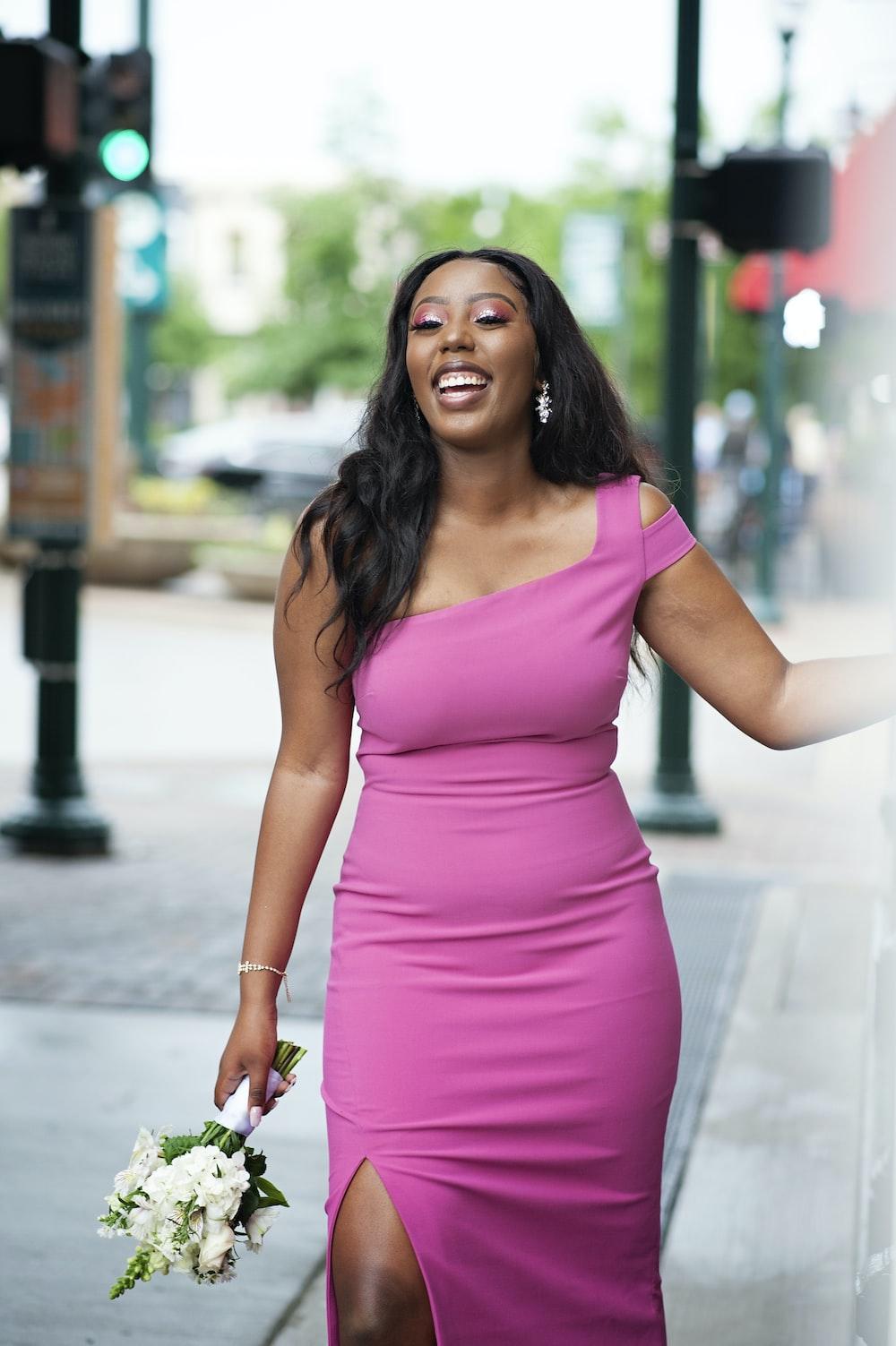 woman in pink sleeveless dress standing on sidewalk during daytime