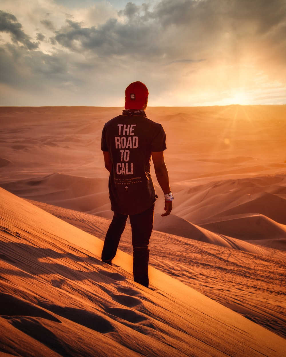 man in black and red hoodie standing on brown sand during daytime
