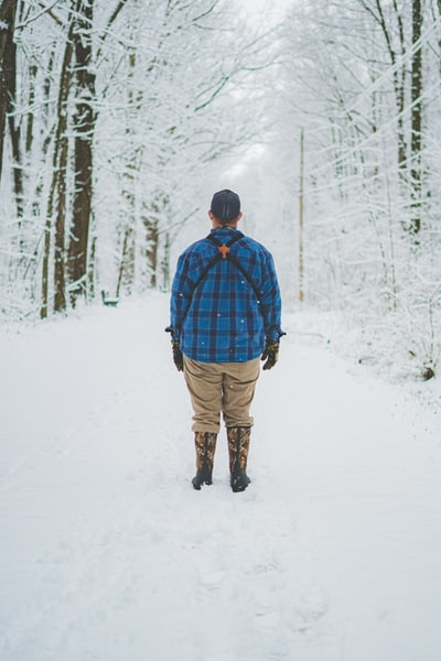 man standing on a snowy trail in the woods