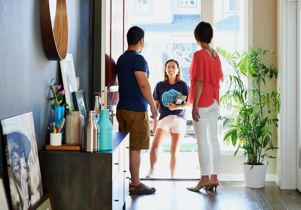 2 women standing beside man in blue t-shirt