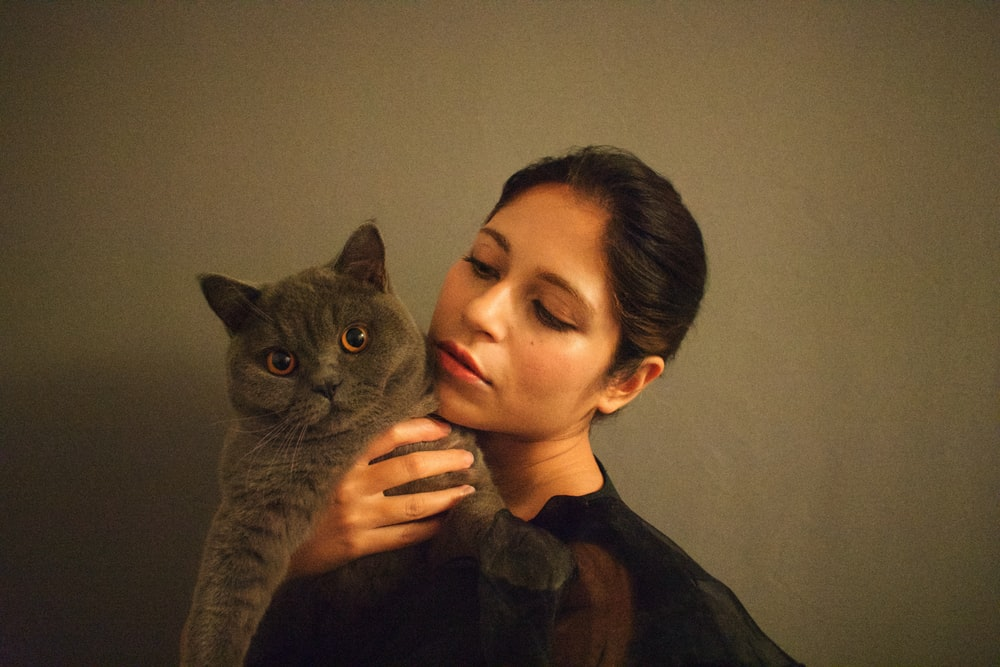 woman in black shirt holding gray cat
