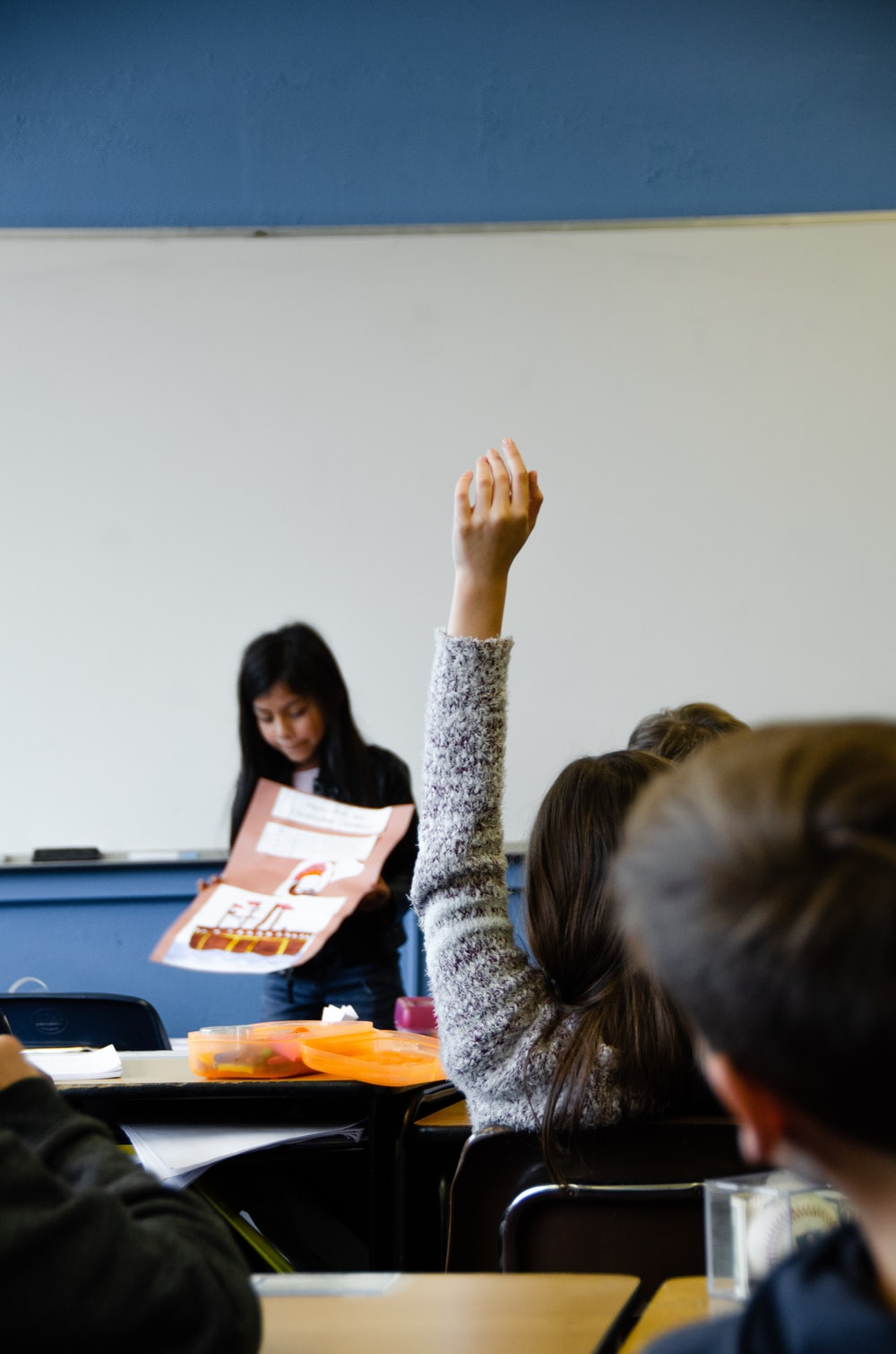teacher on lecture  with a student raising hand