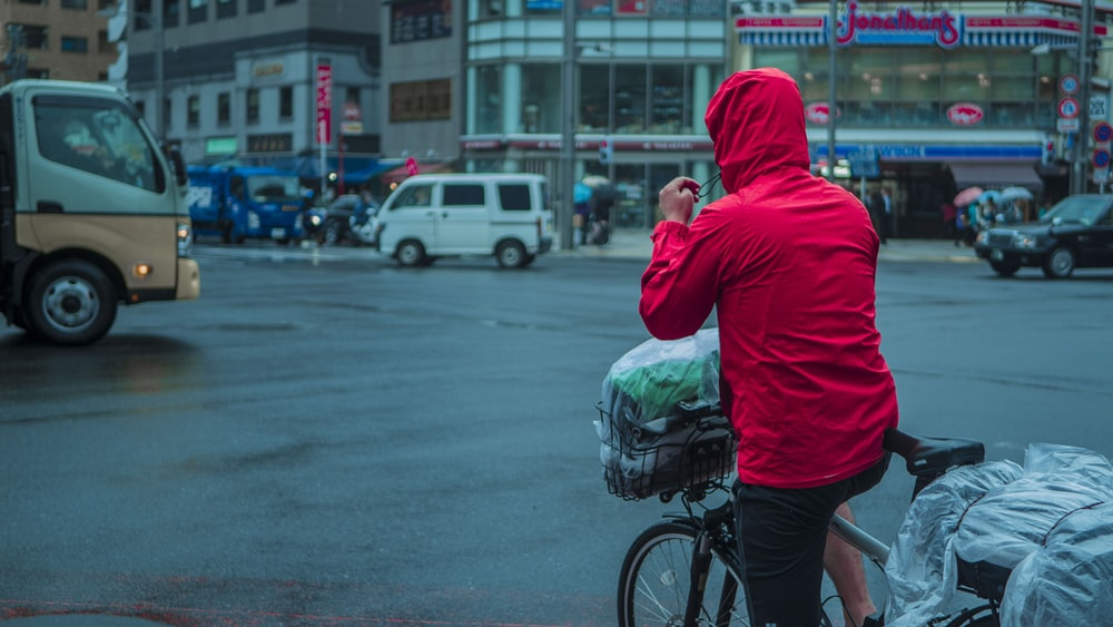 man in red hoodie and black shorts holding green plastic bag