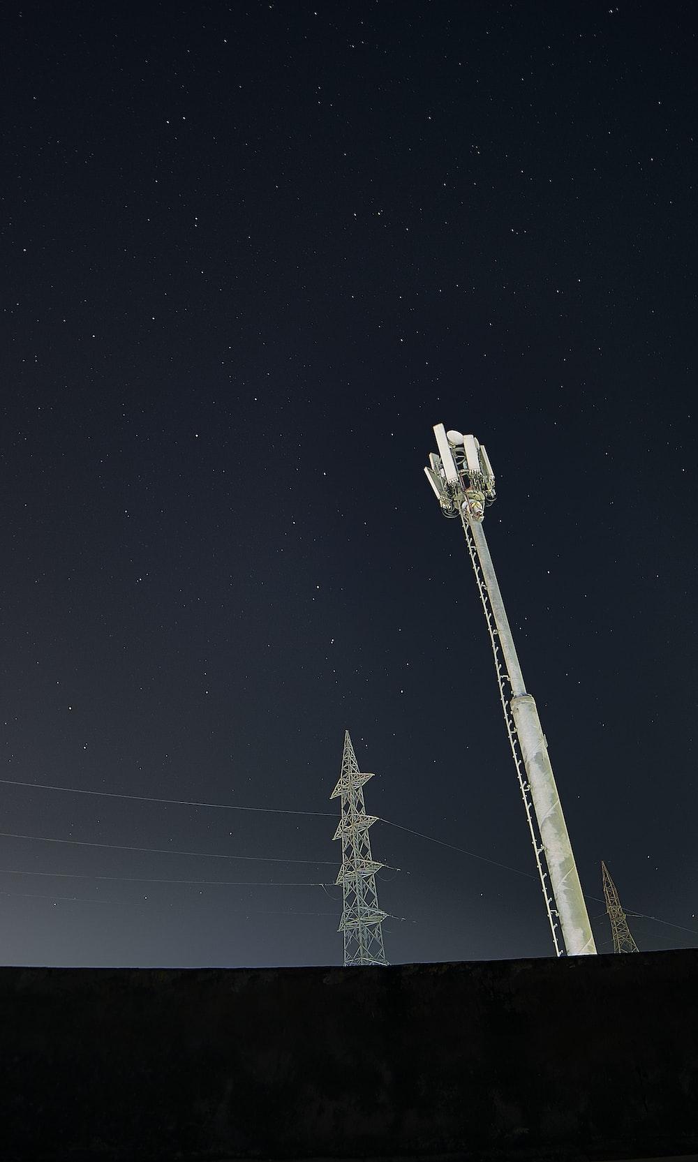white and black satellite tower under black sky