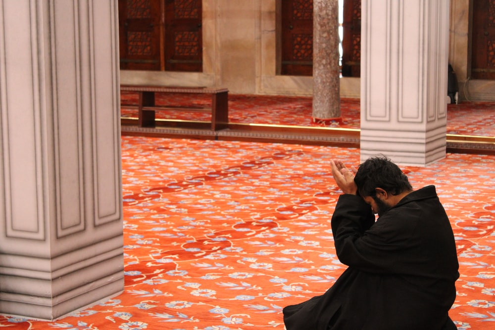 man in black robe sitting on red floor
