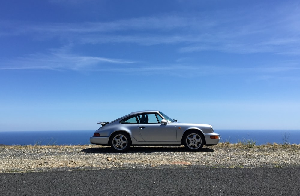 white mercedes benz coupe on gray sand under blue sky during daytime
