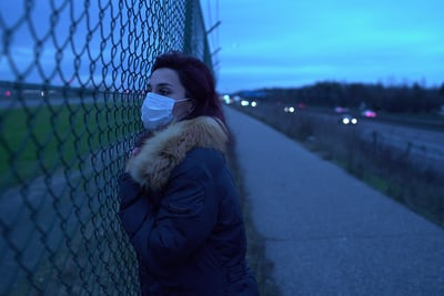 woman in black jacket leaning on black metal fence during daytime