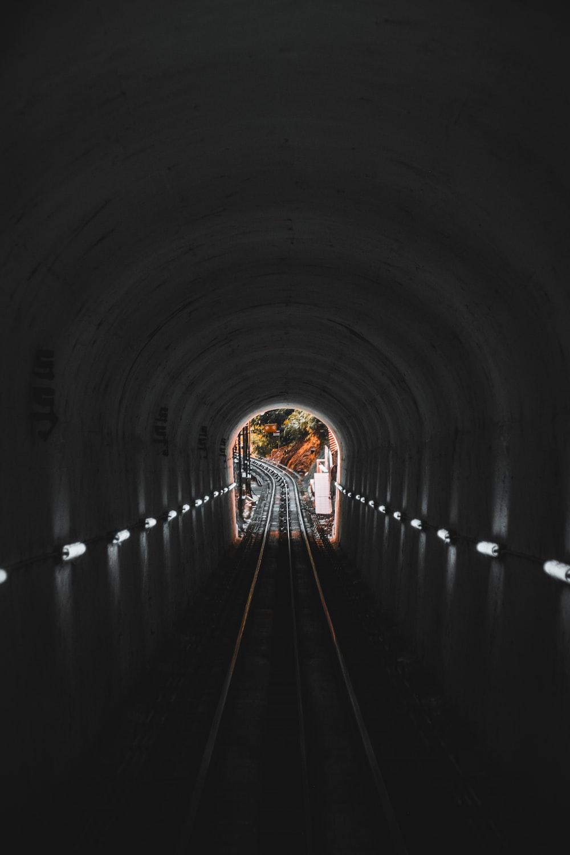 woman in black shirt walking on tunnel
