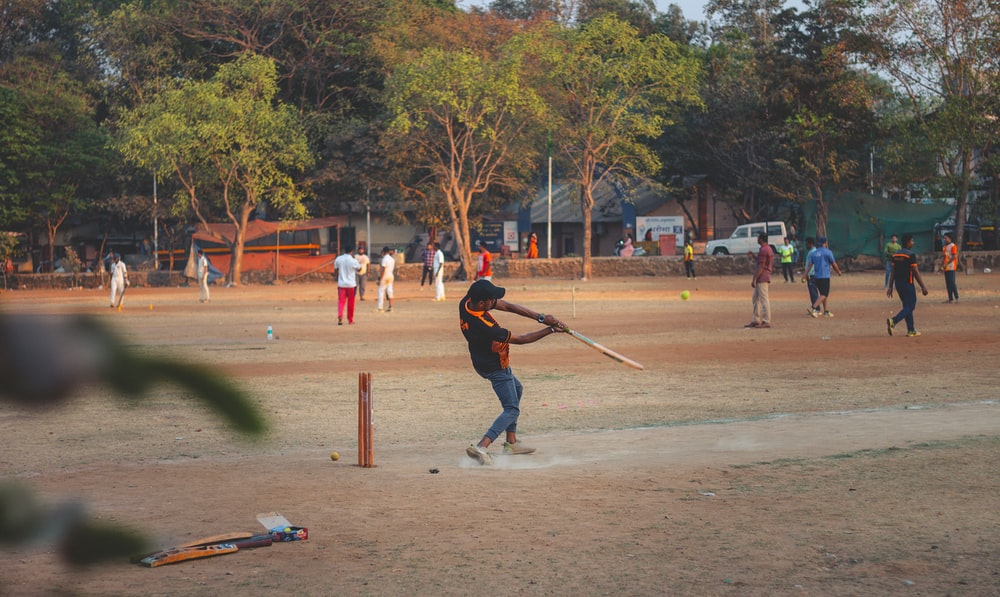 man in red jacket and blue denim jeans playing baseball during daytime