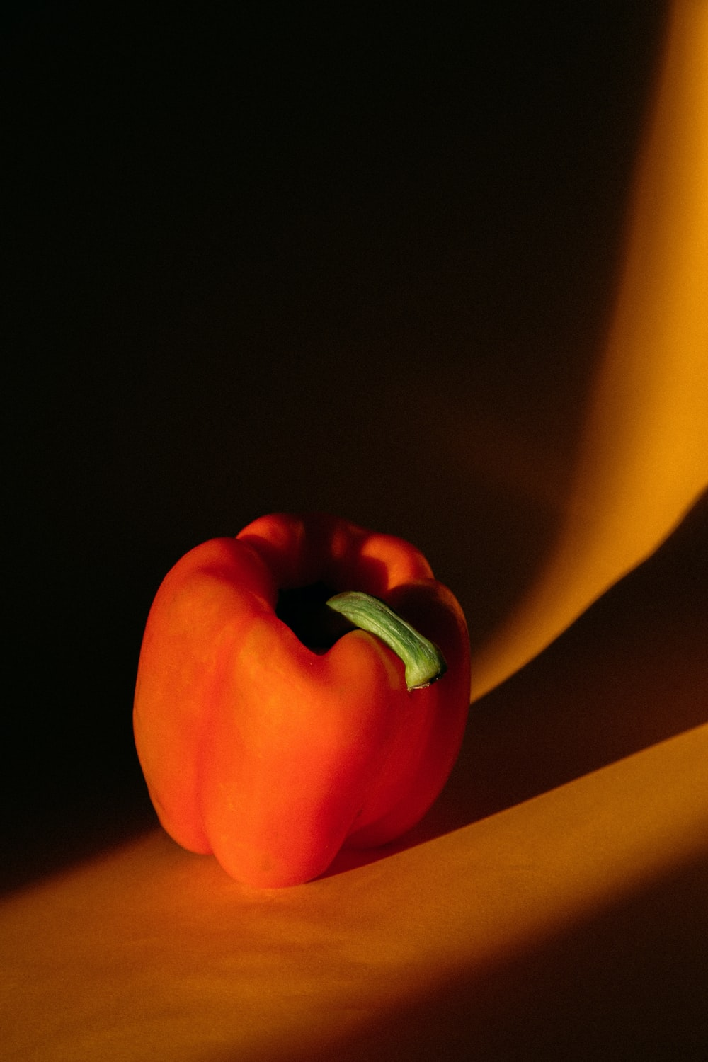 red bell pepper on yellow surface