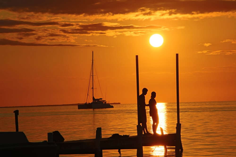 silhouette of 2 people on boat during sunset