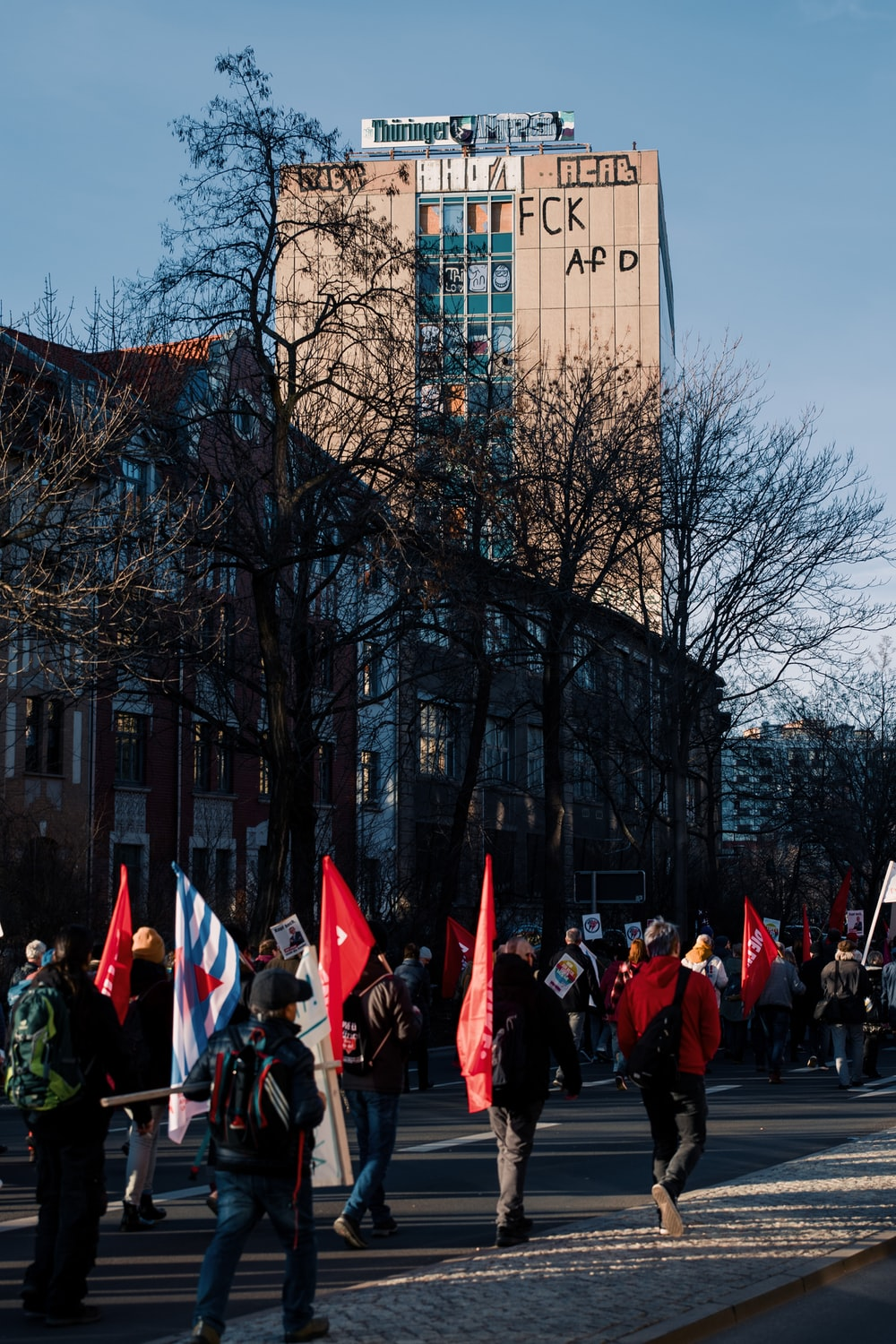 people in red and black suits standing near building during daytime