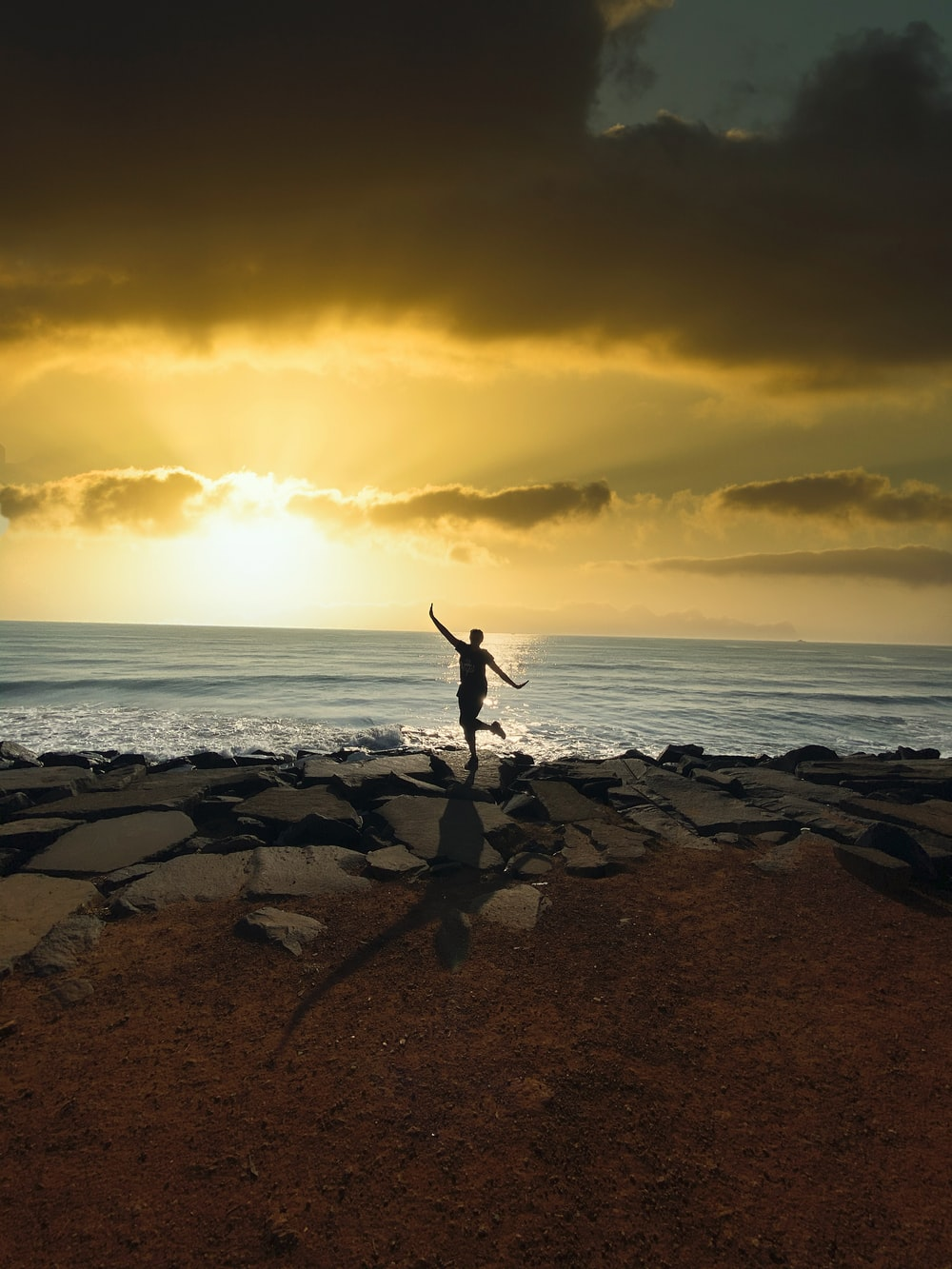 person jumping on rocky shore during sunset