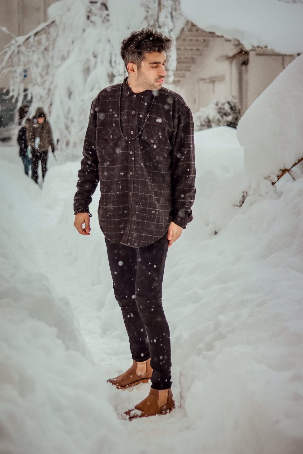 man in black and gray striped coat standing on snow covered ground during daytime