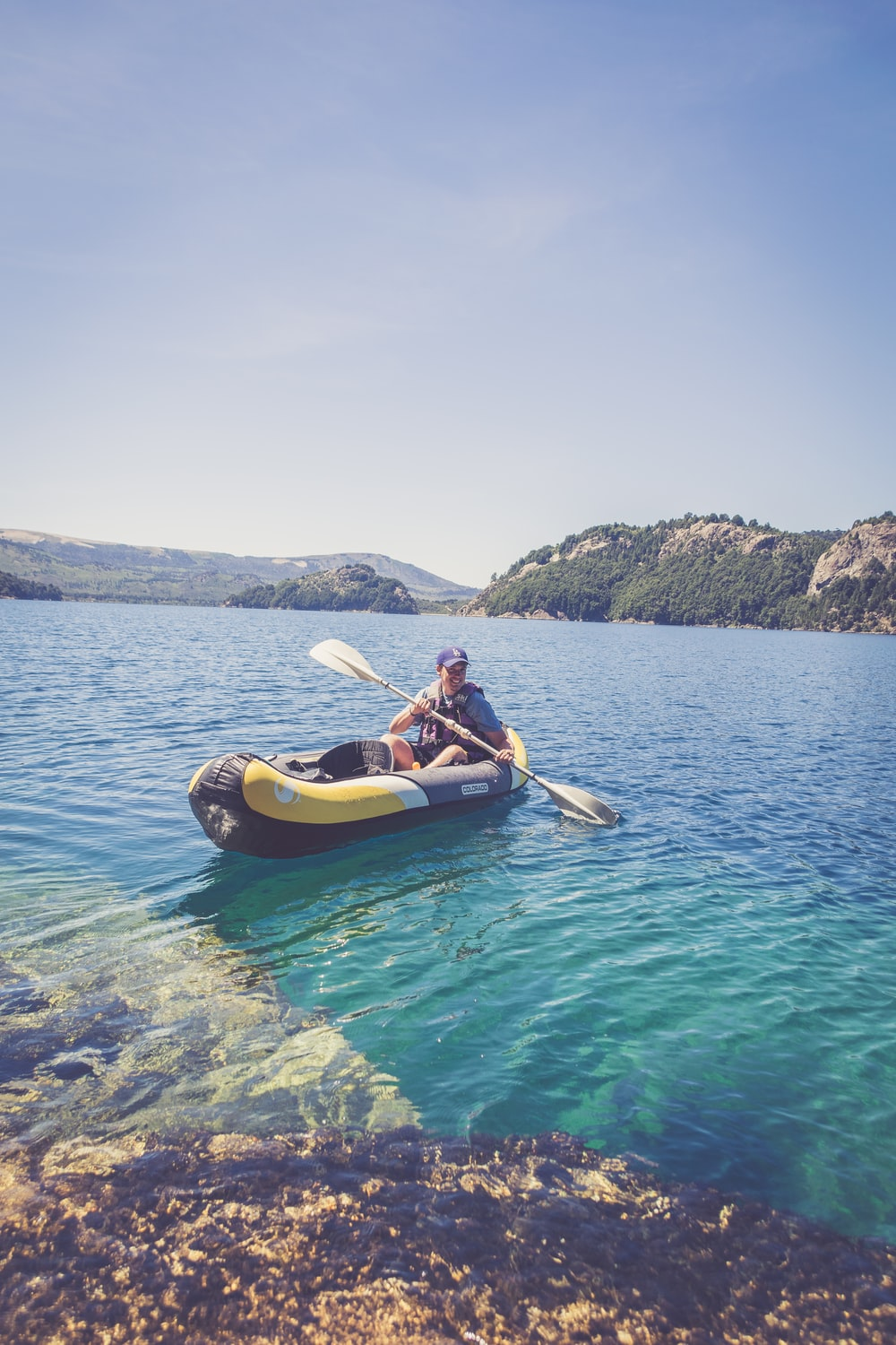 2 person riding on yellow kayak on blue sea during daytime