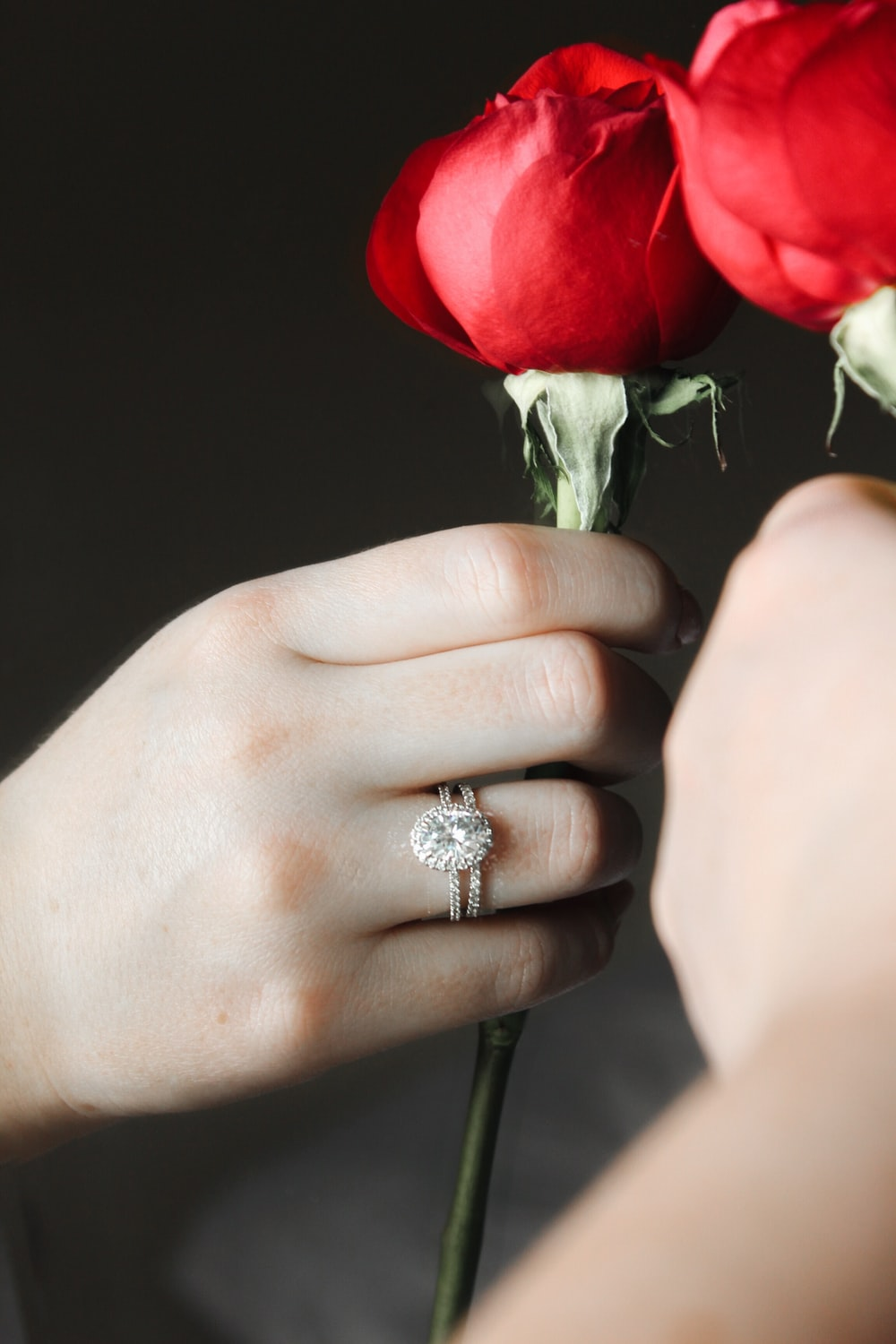 silver diamond ring on persons hand