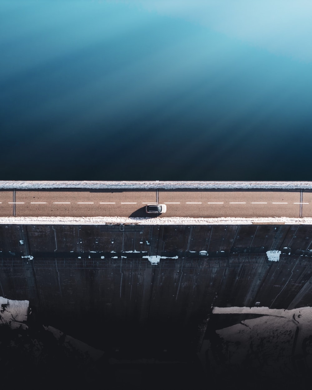 gray concrete wall beside body of water during daytime