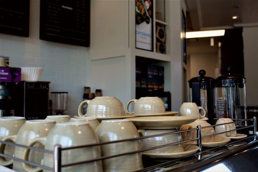 white ceramic mugs on stainless steel rack