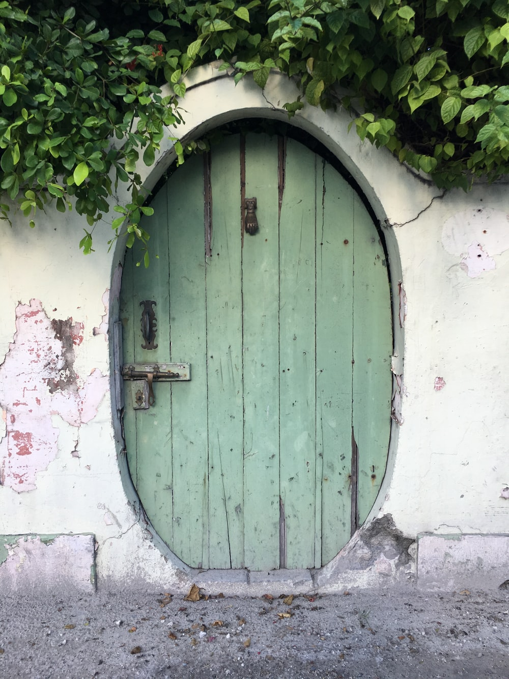 green wooden door on white concrete wall