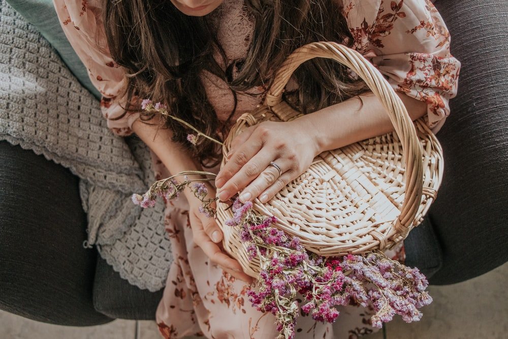 woman in pink and white floral dress holding brown woven basket