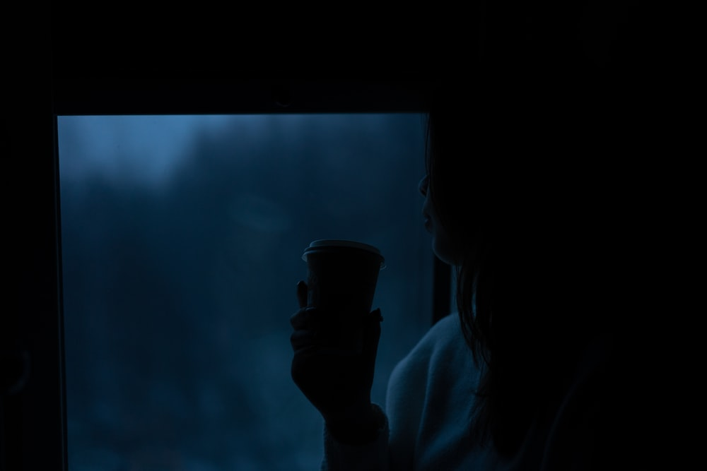 person holding black disposable cup
