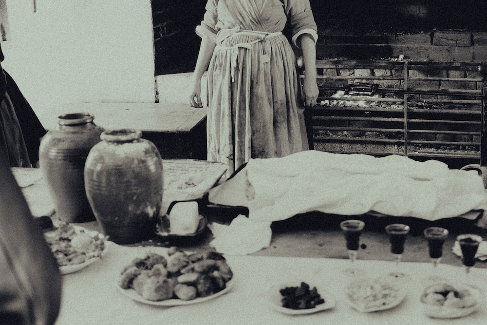 grayscale photo of woman in dress standing in front of cake