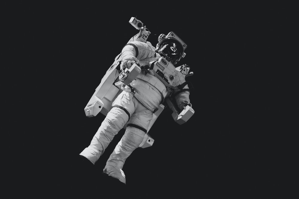 astronaut in white suit in grayscale photography