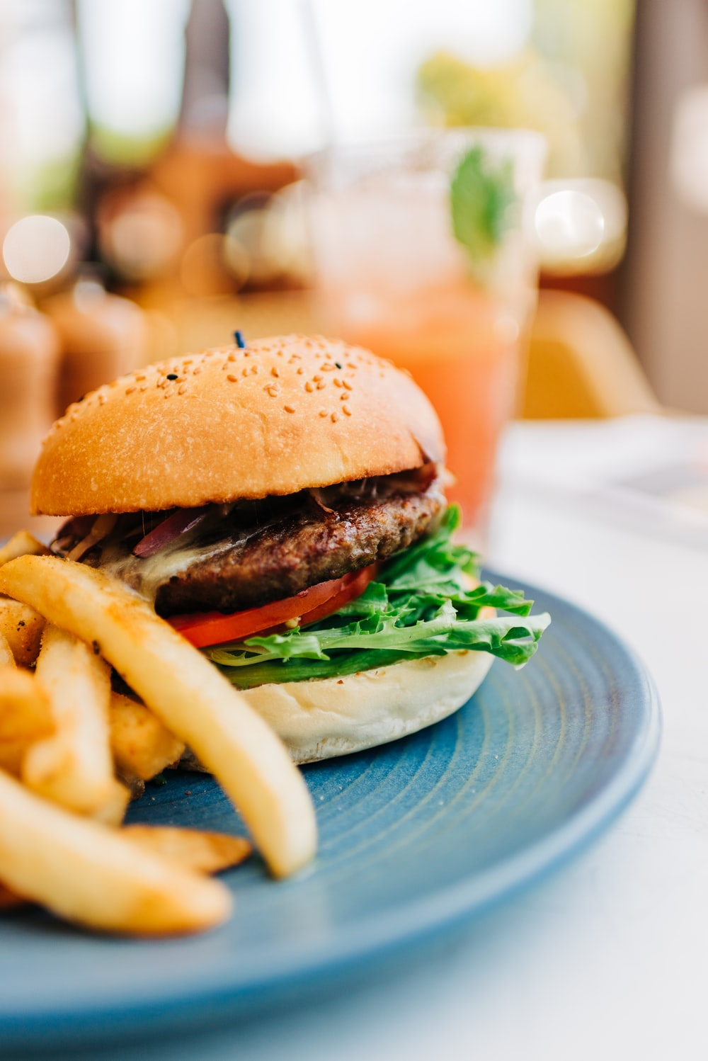 burger with lettuce and tomato on blue ceramic plate