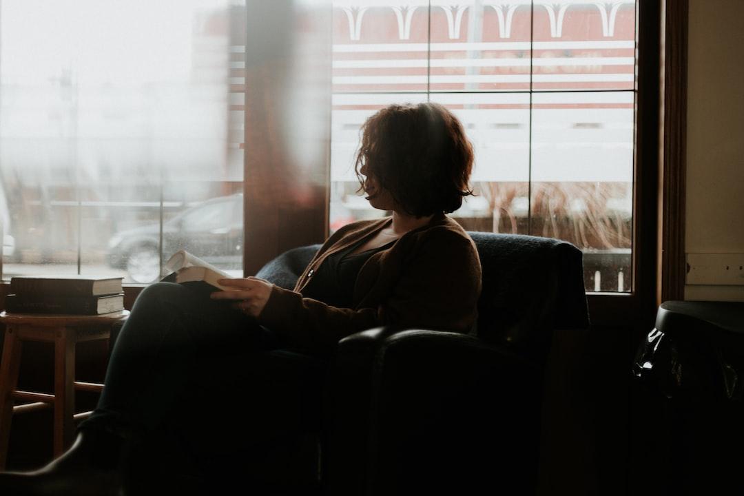 Woman In Black and Brown Plaid Long Sleeve Shirt Sitting On Black Sofa - unsplash