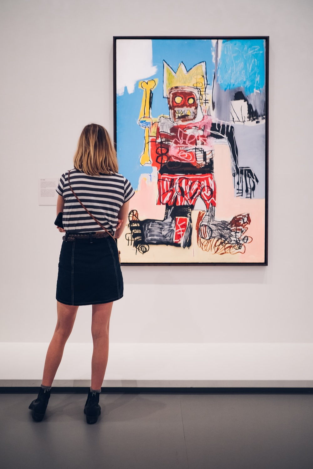 woman in black and white striped shirt standing in front of abstract painting