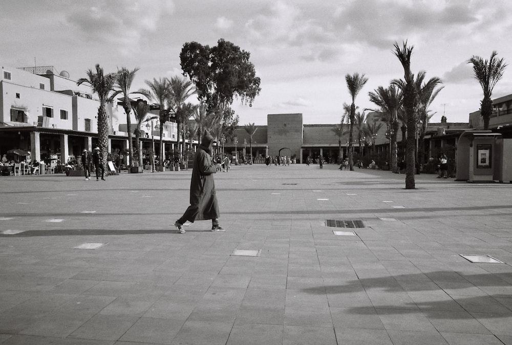 grayscale photo of woman walking on sidewalk near palm trees