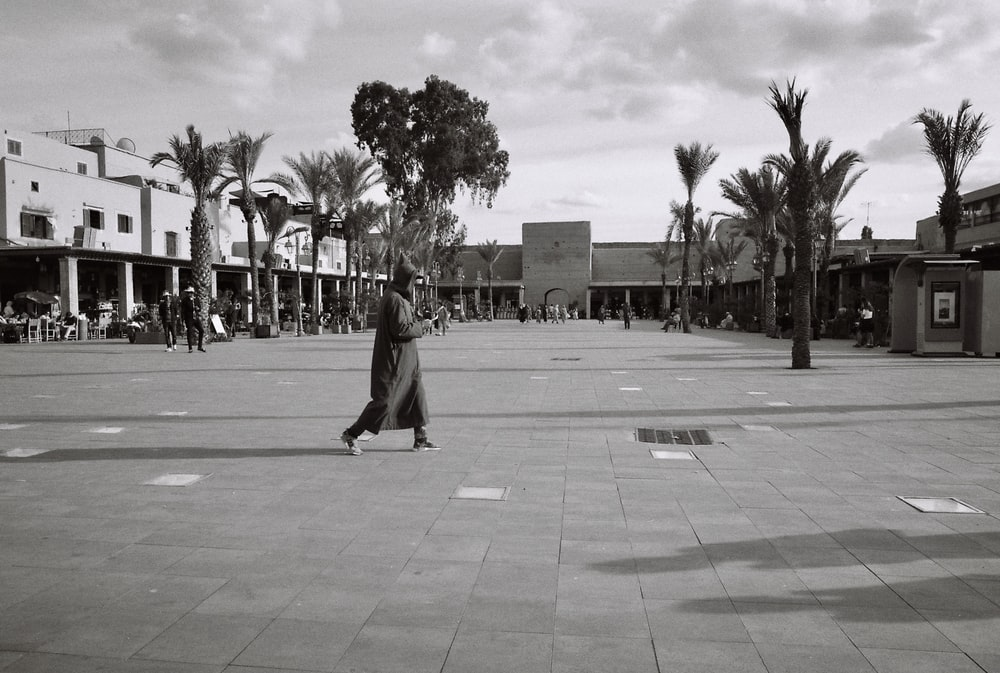 grayscale photo of woman walking on sidewalk near palm trees