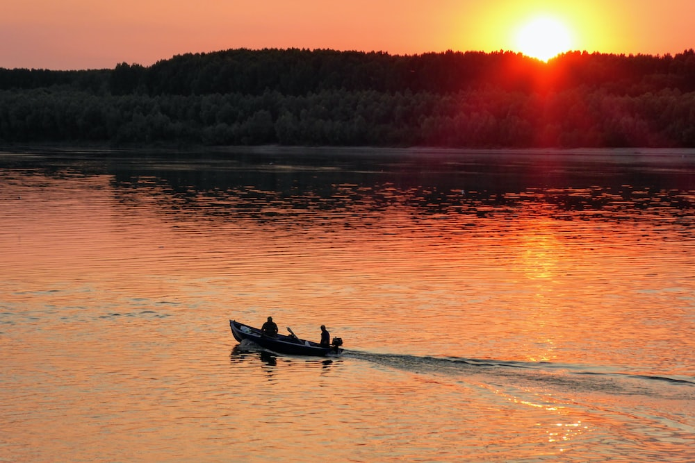 2 people riding on boat on body of water during sunset