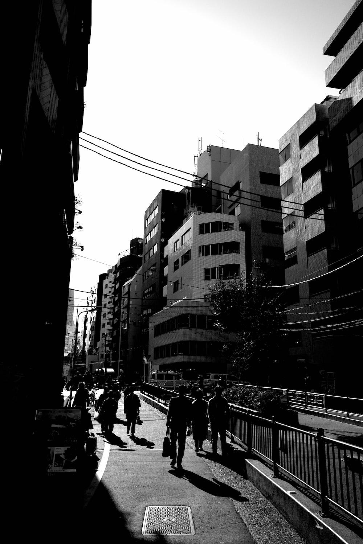 grayscale photo of people walking on street between buildings