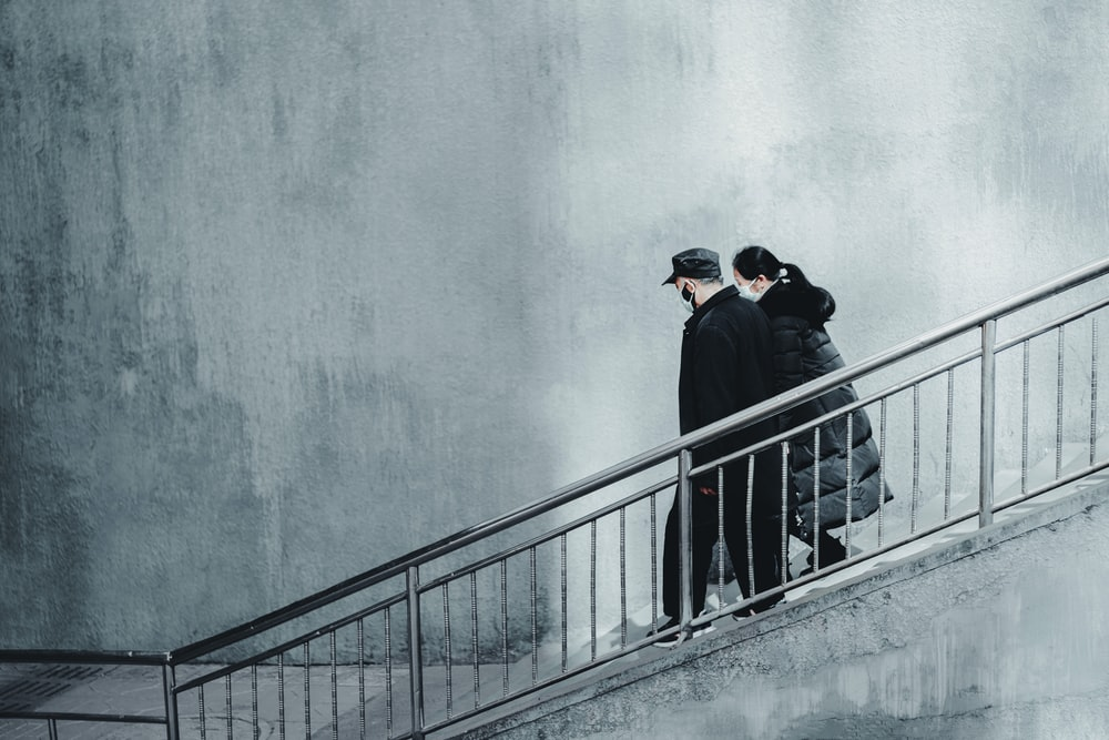 man in black jacket and black cap standing on gray concrete staircase
