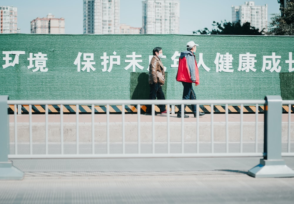 2 women standing on gray concrete road during daytime