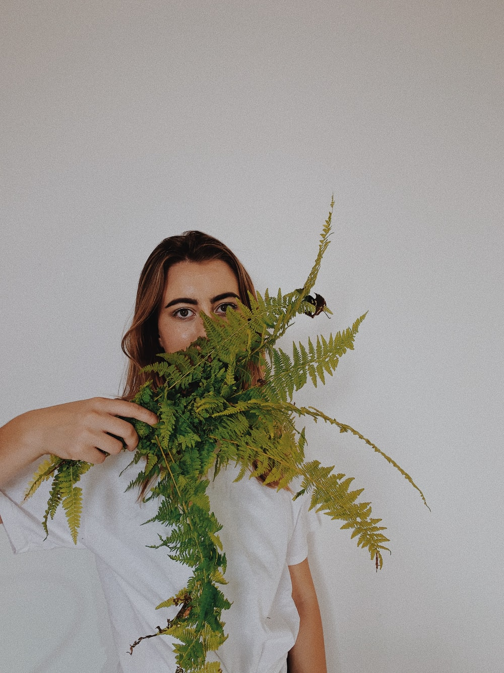 woman in white crew neck t-shirt holding green plant