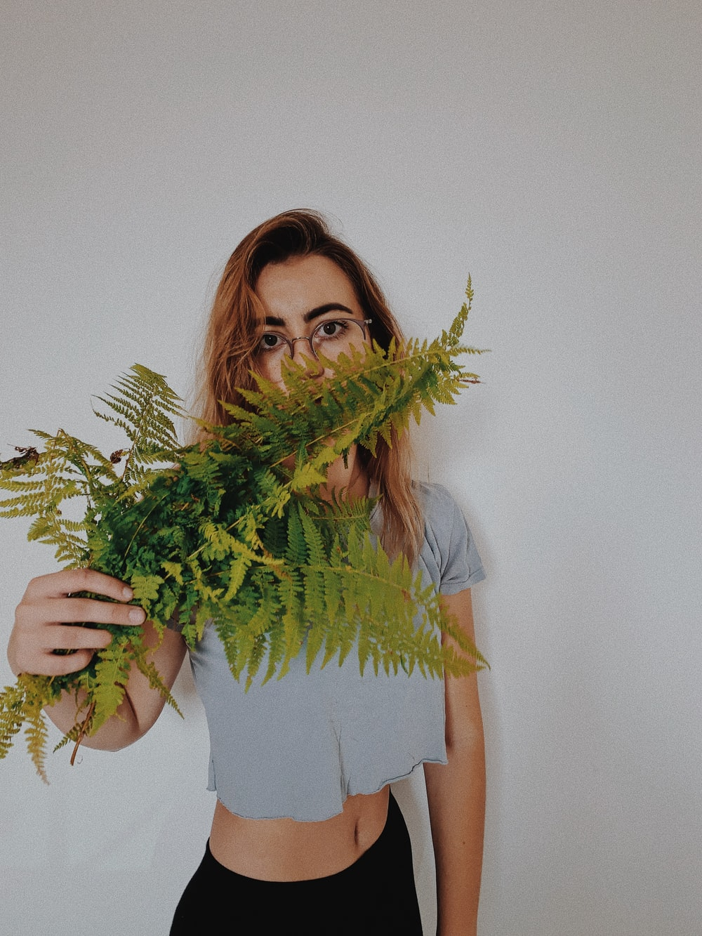 woman in blue t-shirt holding green plant