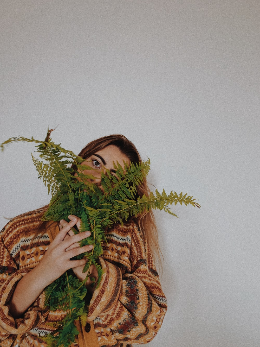 woman in brown and black leopard print scarf holding green plant
