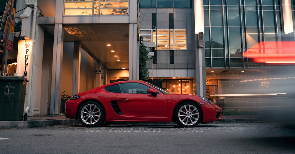 red ferrari 458 italia parked near brown building