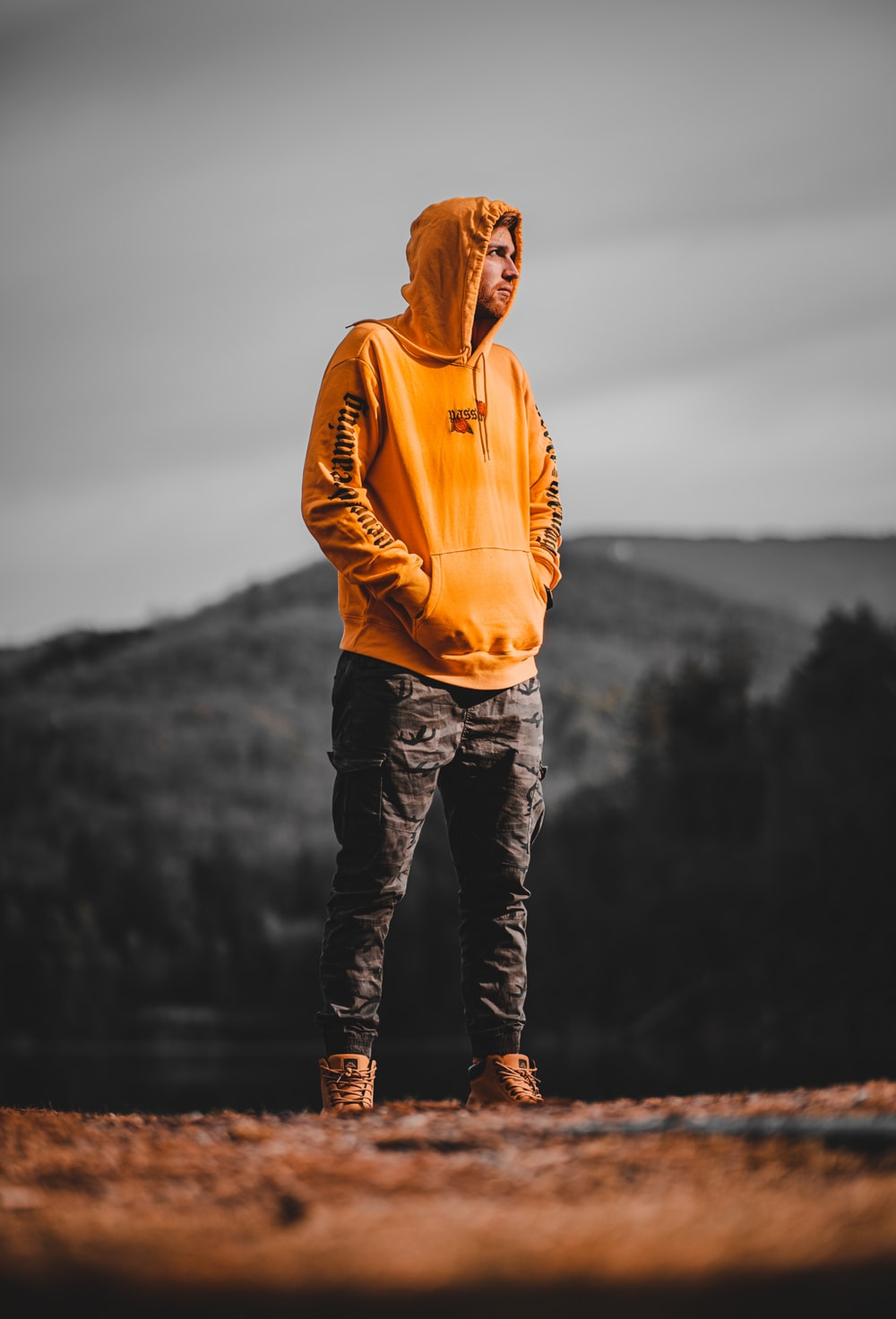 man in orange hoodie standing on rock near body of water during daytime