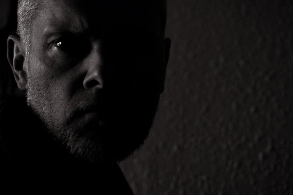 man in black shirt near brown wall
