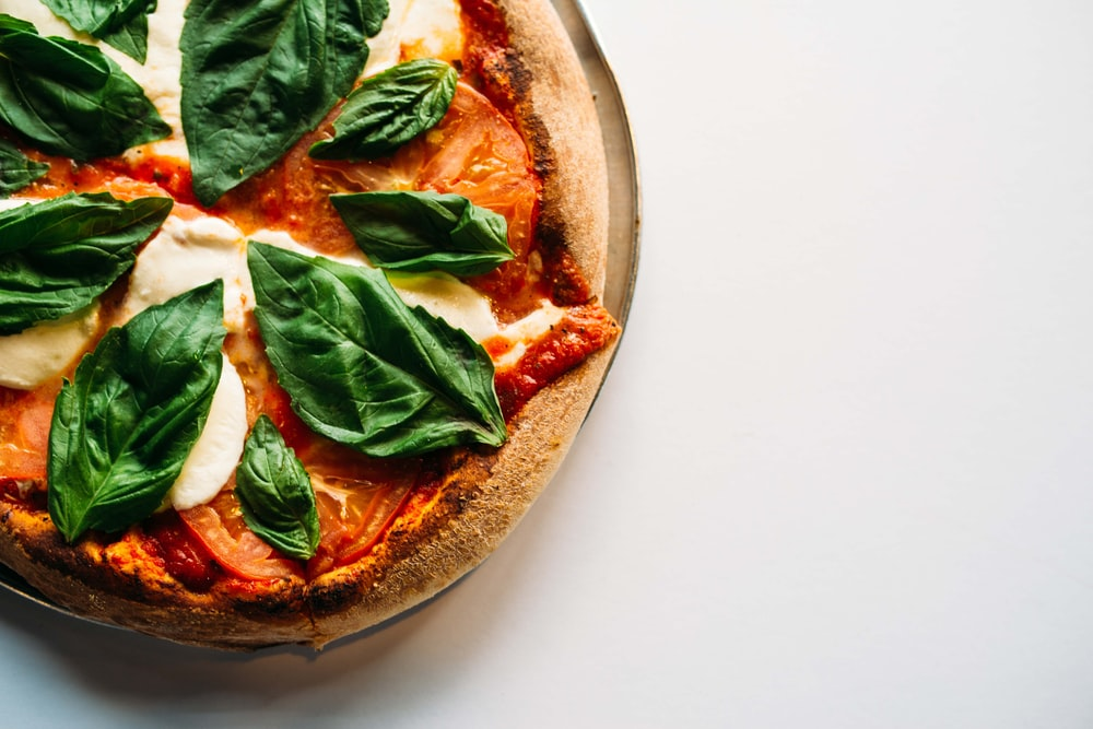 pizza with green leaves on white ceramic plate