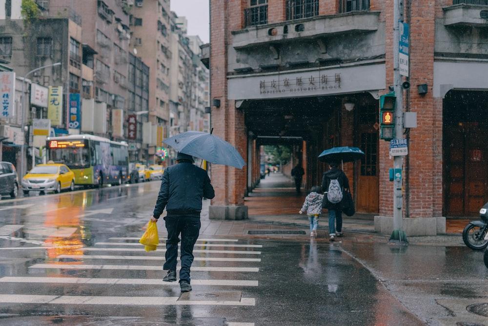person in black jacket and yellow pants holding umbrella walking on pedestrian lane during daytime
