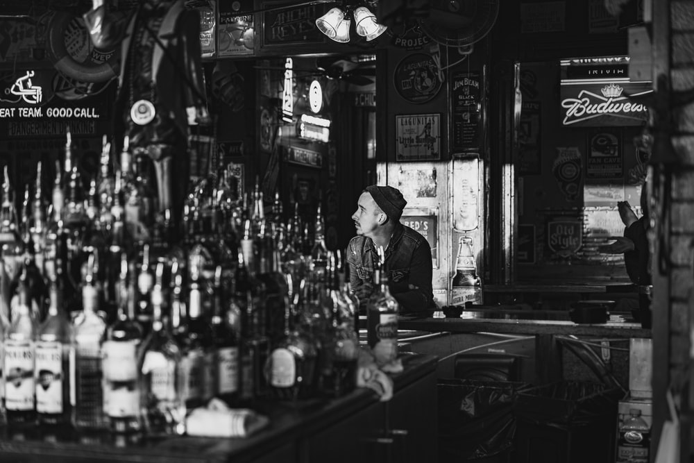 man in black and white long sleeve shirt standing near bar counter