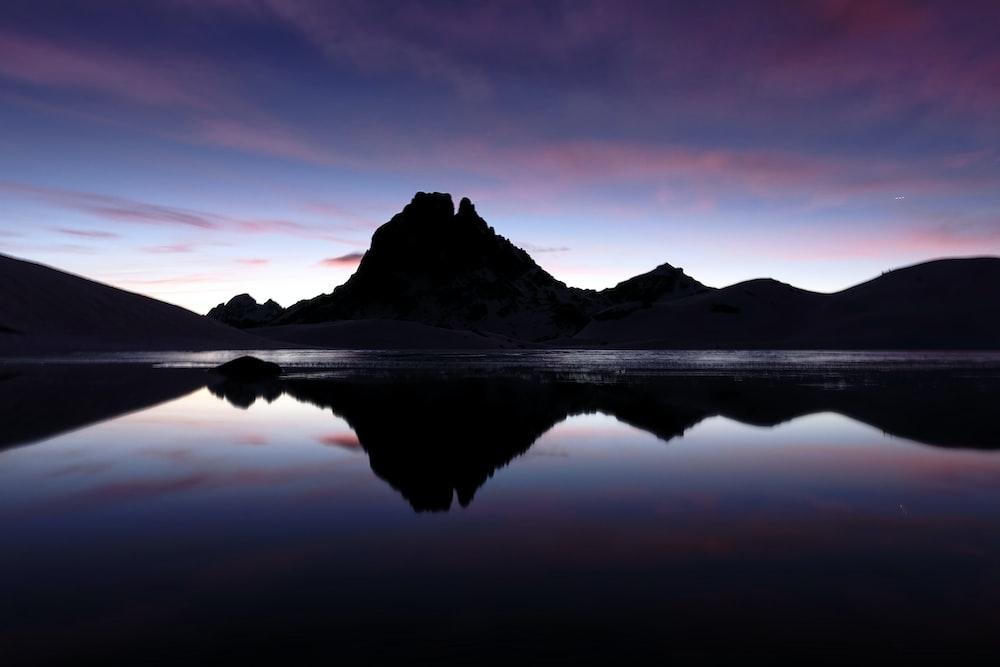 body of water near mountain during daytime