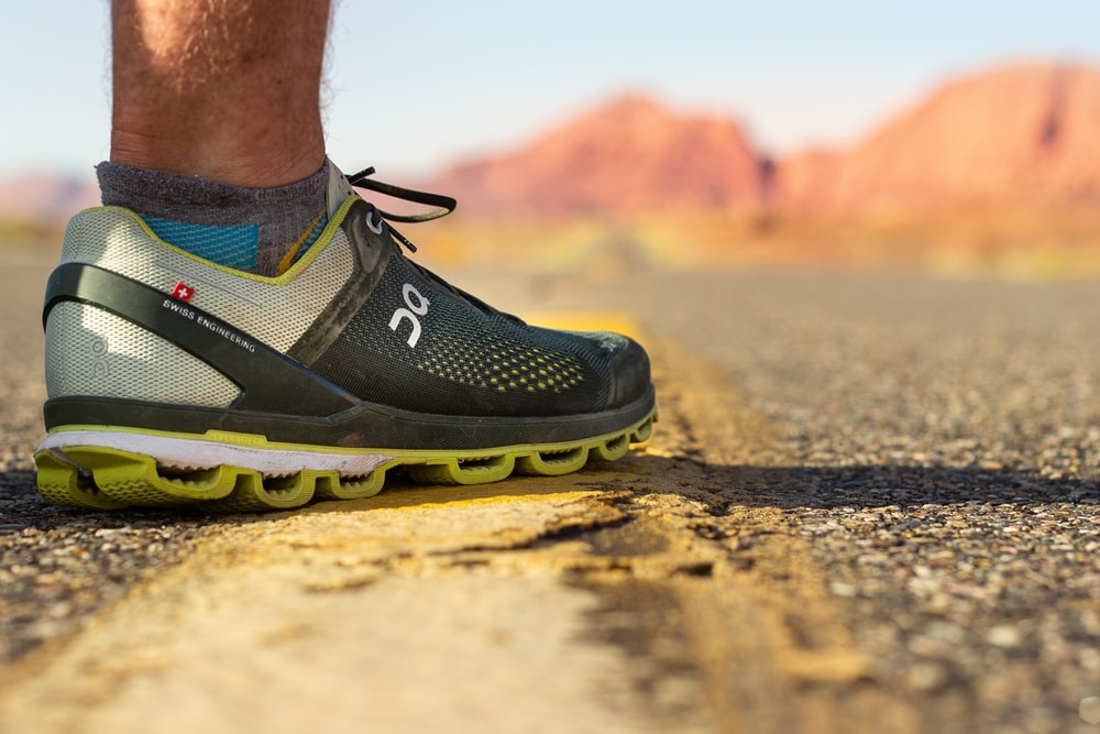 person wearing black and yellow nike running shoes